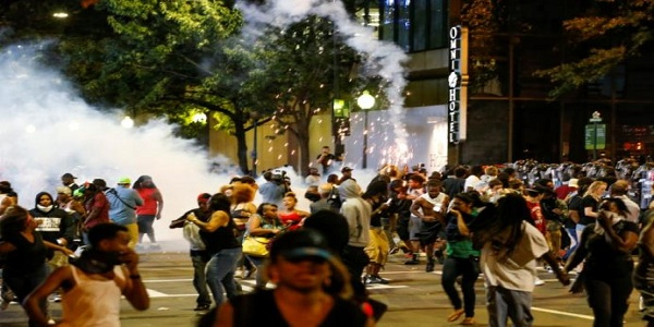 People run from flash-bang grenades in uptown Charlotte, NC during a protest of the police shooting of Keith Scott, in Charlotte
